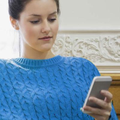 Visuel d'une jeune femme qui regarde son smartphone - Bouygues Telecom