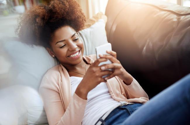 Visuel jeune fille avec un smartphone dans un canape   Bouygues Telecom