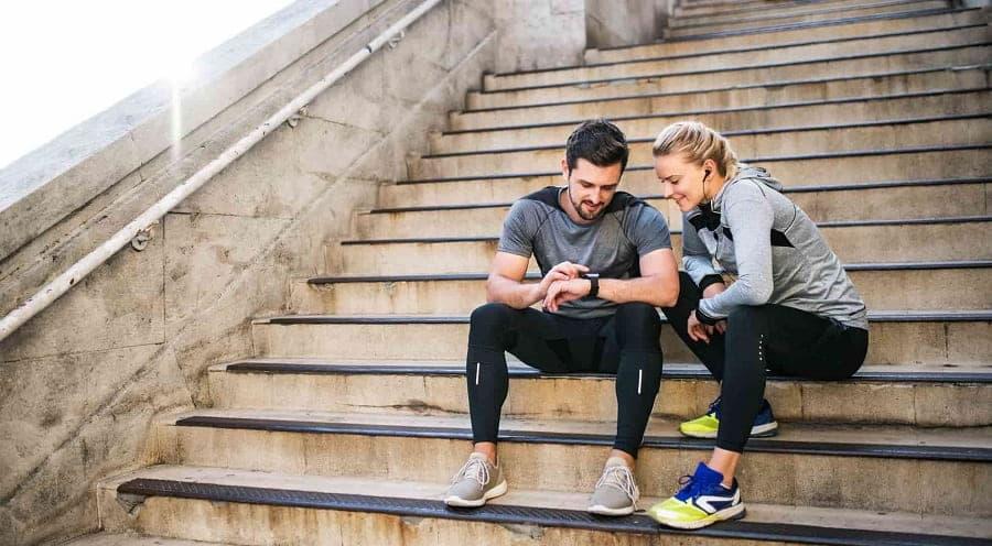 couple sportif homme femme montre connectee escalier