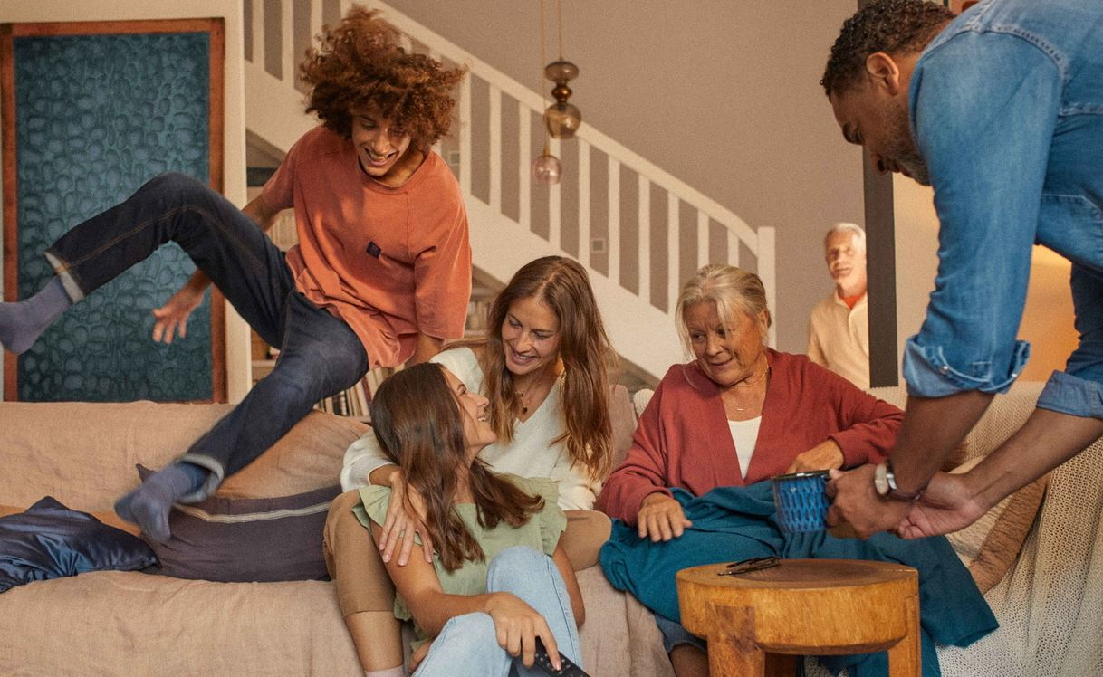 Famille réunie sur le canape avec un jeune qui saute
