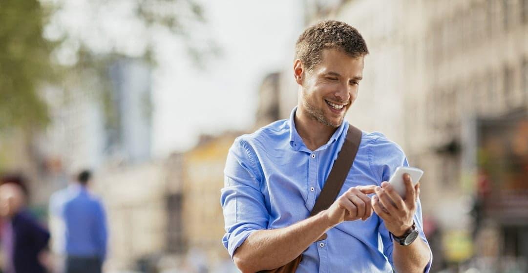 homme chemise utilisant smartphone rue