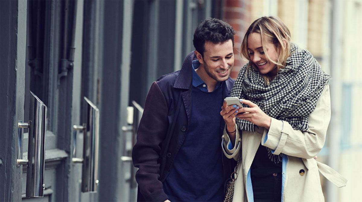 image de couple homme femme utilisant smartphone dehors