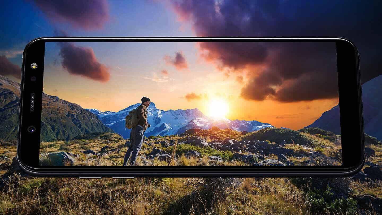 """Le galaxy A6 est placé à l' horizontal devant un paysage montagneux sur lequel se lève le soleil. L""""écran est lumineux et coloré."""