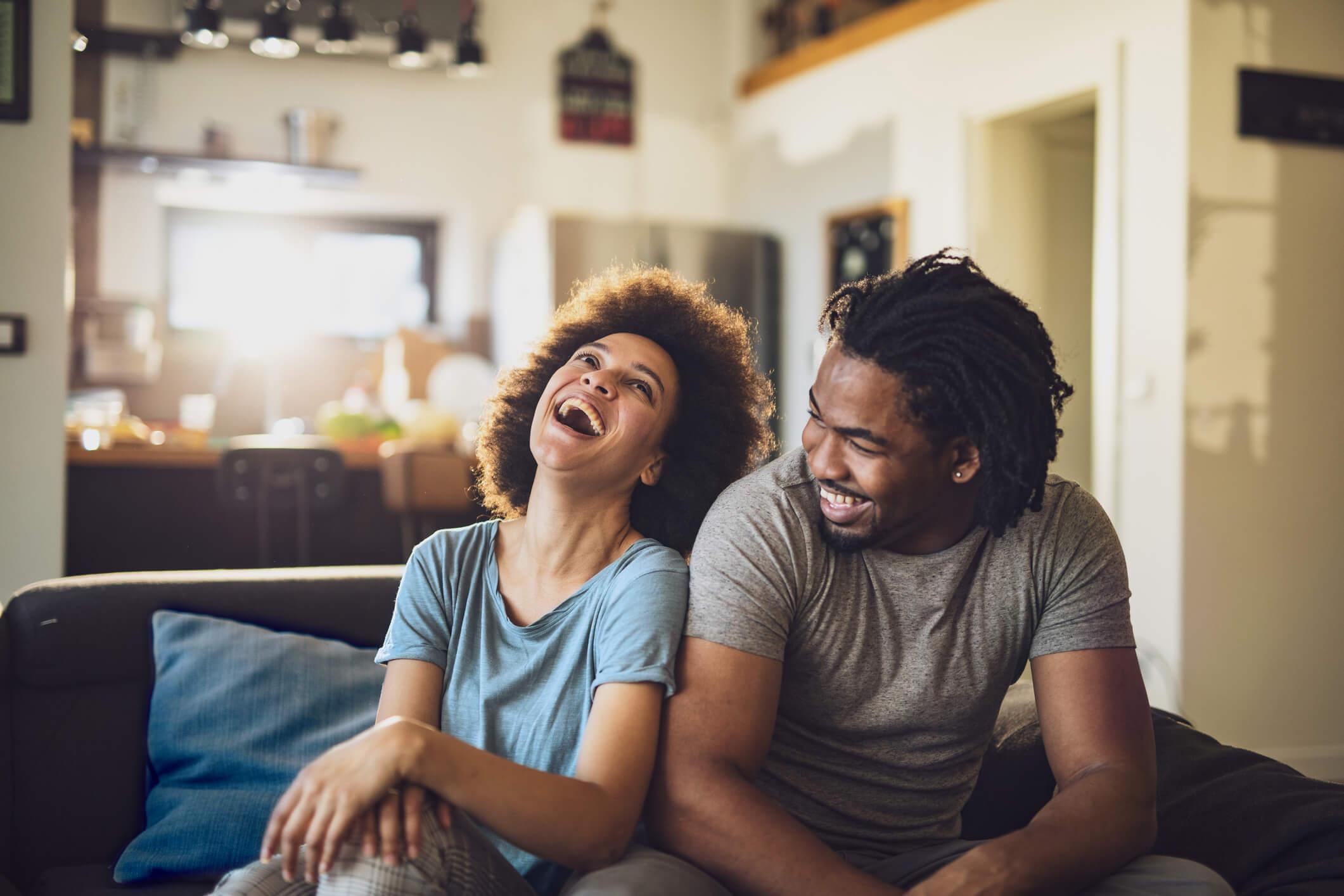 visuel Jeune couple riant assis sur un canapé