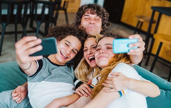Famille heureuse prenant un selfie sur le canape du salon