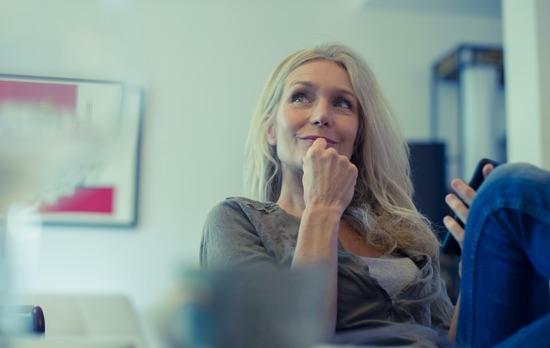 Femme souriante smartphone en main salon