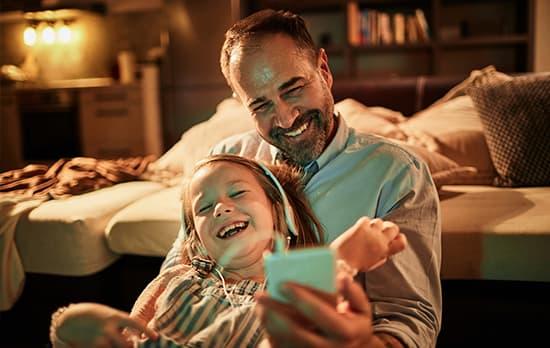 Homme et petite fille jouant avec smartphone dans chambre