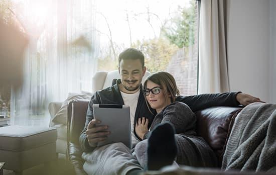 Jeune couple regardant film sur tablette dans le salon