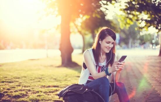Femme assise utilisant smartphone dans un parc