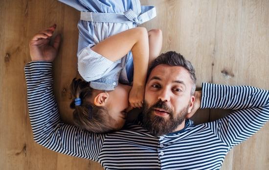 Pere et fille jouant allonge au sol