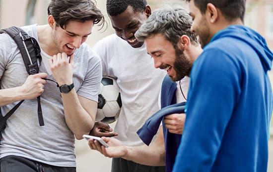 quatre jeunes sportifs regardant un smartphone
