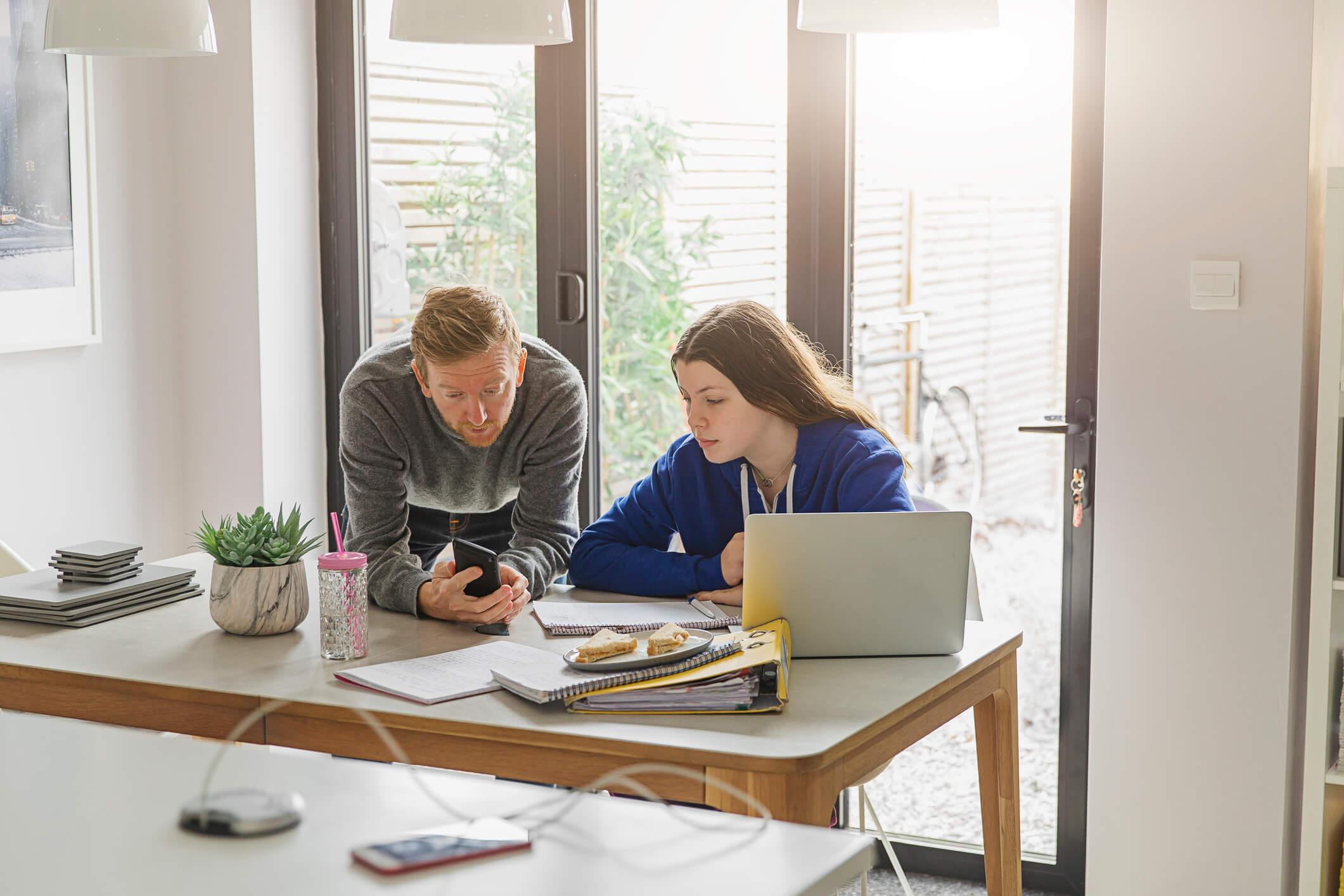 Père et fille regardant smartphone et ordinateur dans un bureau lumineux du domicile