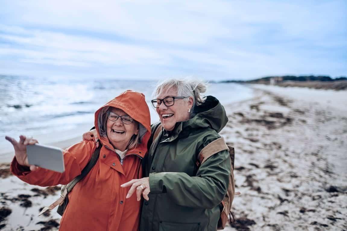 Visuel de deux femmes agées en camping prenant un selfie