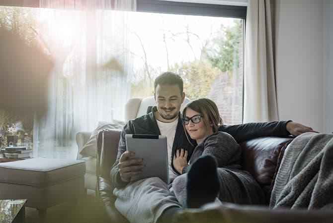 couple d age mur regardant une tablette sur le canape du salon