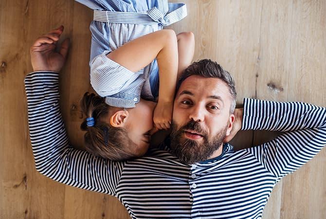 une femme et son fils regardant une tablette sur le canape du salon