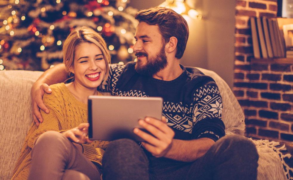 Image de deux personnes heureuses avec une tablette pour les fêtes - Bouygues Telecom