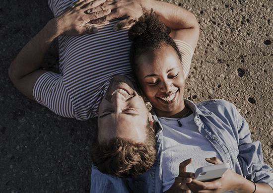 Visuel couples allongé avec un smartphone