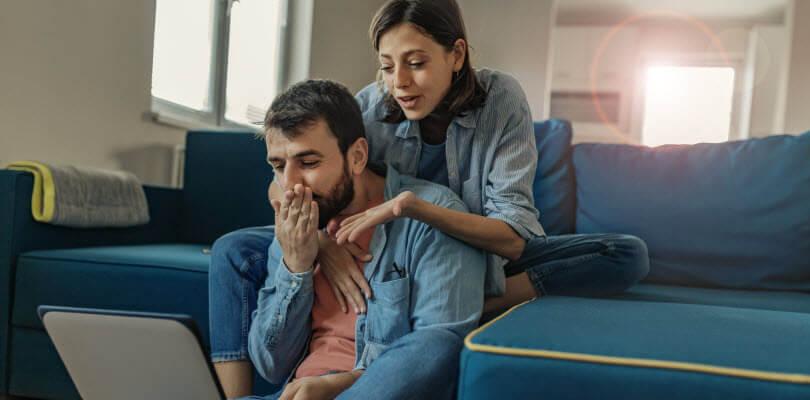 couple jouant sur ordi portable dans leurs salon ensoleillé