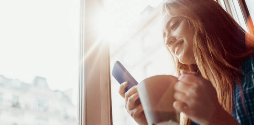 femme buvant café et regardant son smartphone