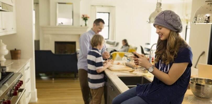 fille avec smartphone en famille à la maison