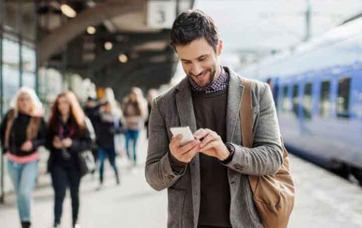 Homme souriant avec smartphone dans une gare