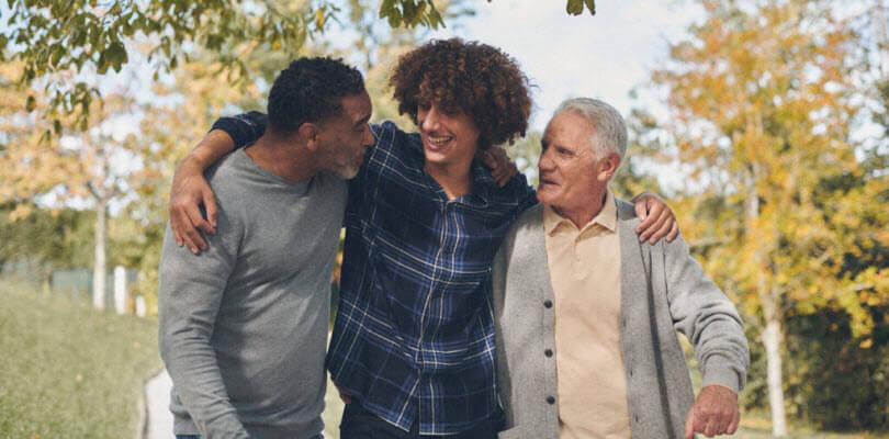 père fils et grand-père souriant et marchant dans le jardin