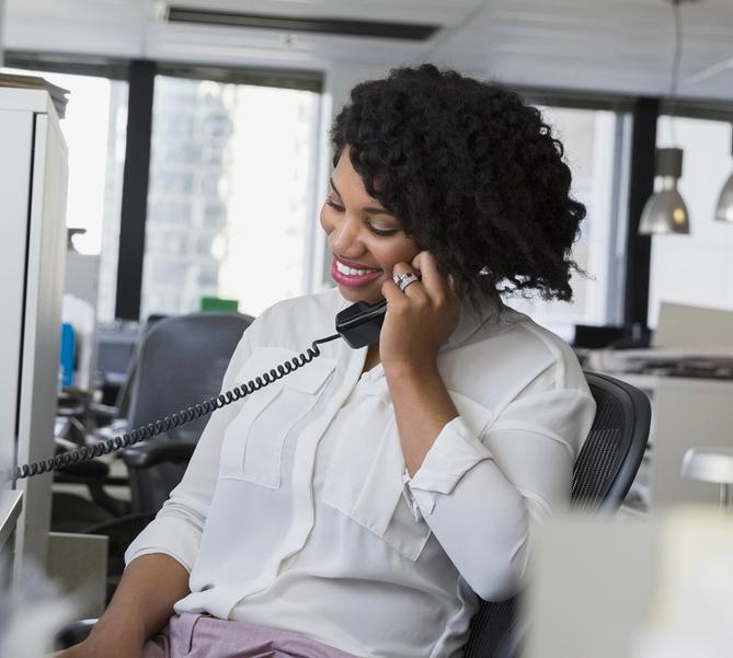 Image d'une femme heureuse grâce aux services téléphoniques pour les Pros