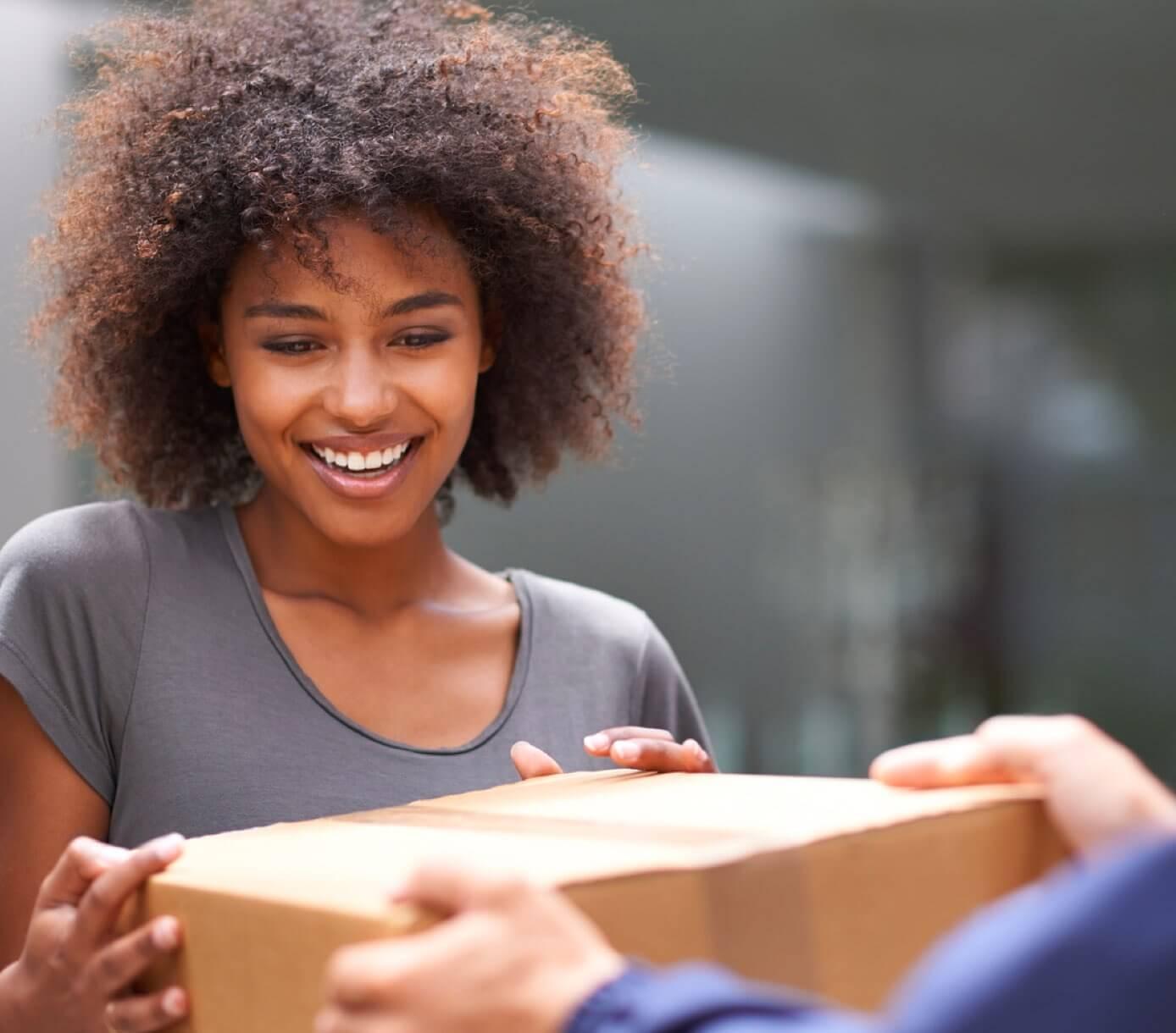 Jeune femme souriant à la réception de son colis